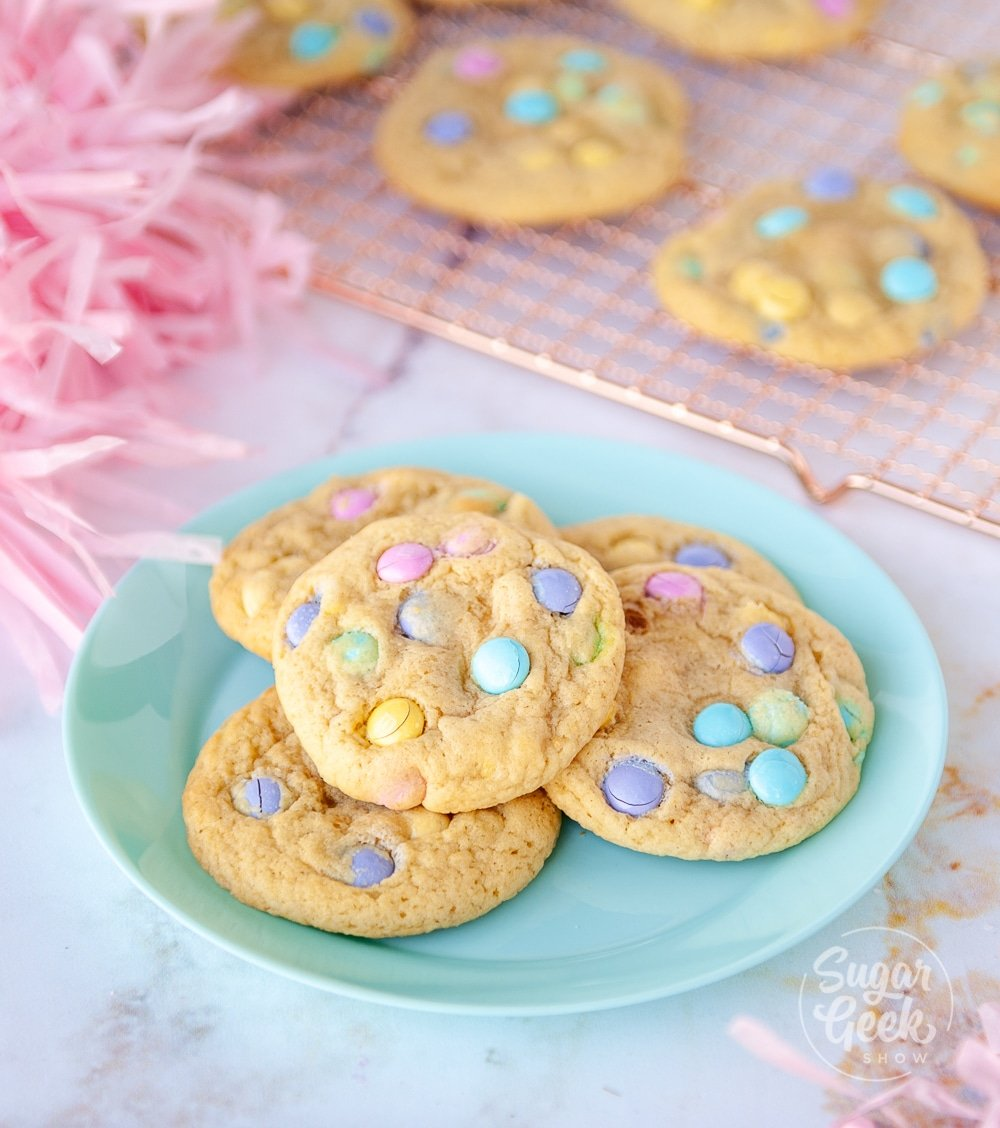 M&M cookies on a blue plate with more cookies on a cooling rack behind the plate