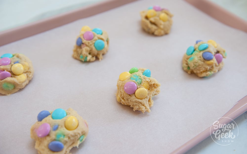 M&M cookie dough balls on a parchment covered cookie sheet