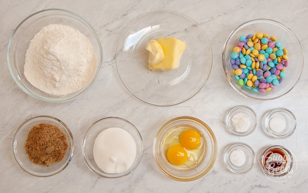 ingredients for M&M cookies in clear bowls on a white background shot from above