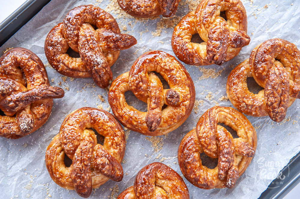 freshly baked pretzels on baking sheet with white parchment paper