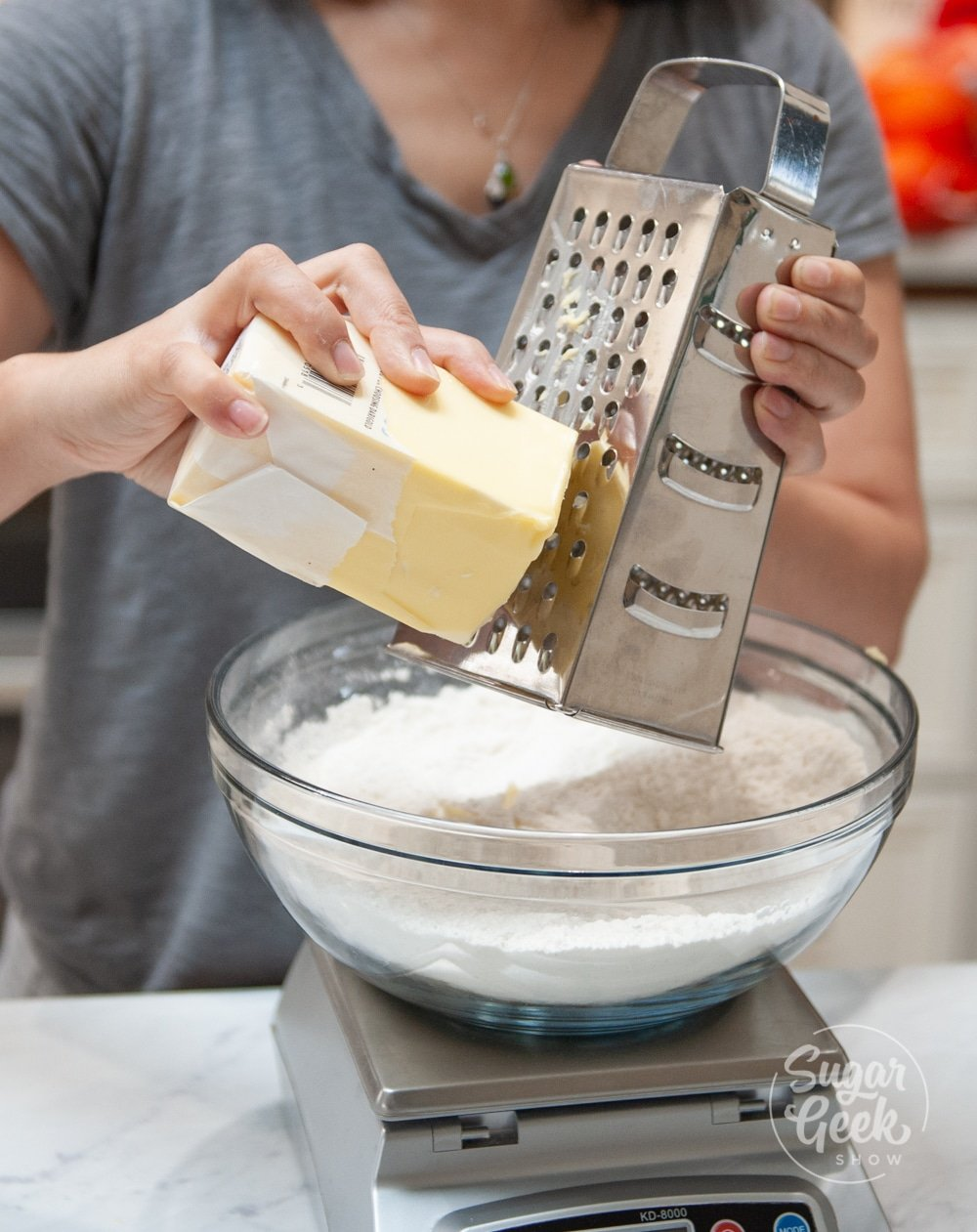 shredding cold butter into dry ingredients on top of a scale