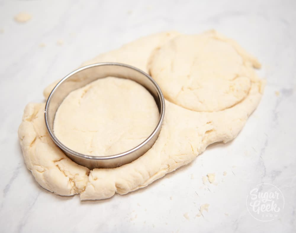 metal cutter cutting out biscuits from leftover dough