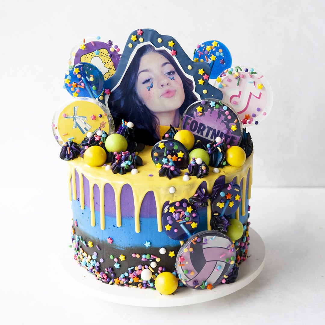 Cake with all kinds of lollipops, logos and icons, a topper of a birthday girl and a ganache drip with sprinkles