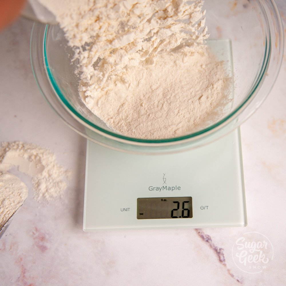 flour being added to a clear mixing bowl on top of a digital kitchen scale