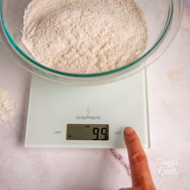 flour in a clear bowl on top of a digital kitchen scale