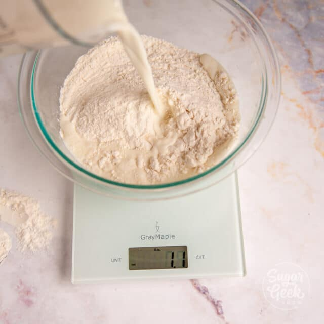 milk being poured into a bowl of flour on a digital kitchen scale