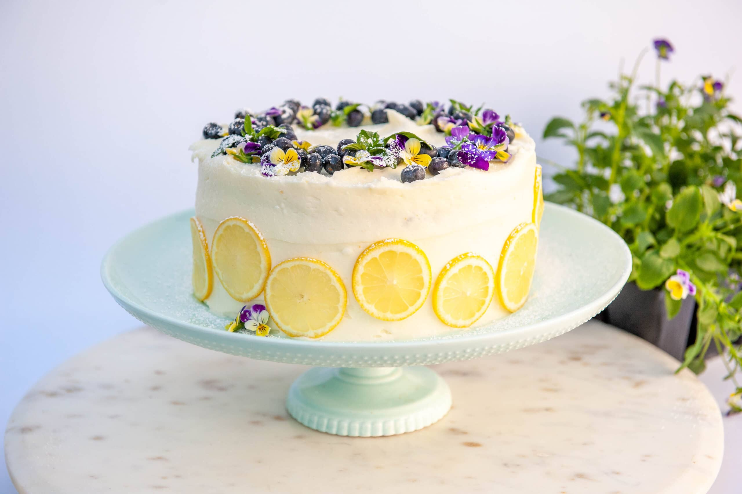 lemon blueberry layer cake on light blue cake stand