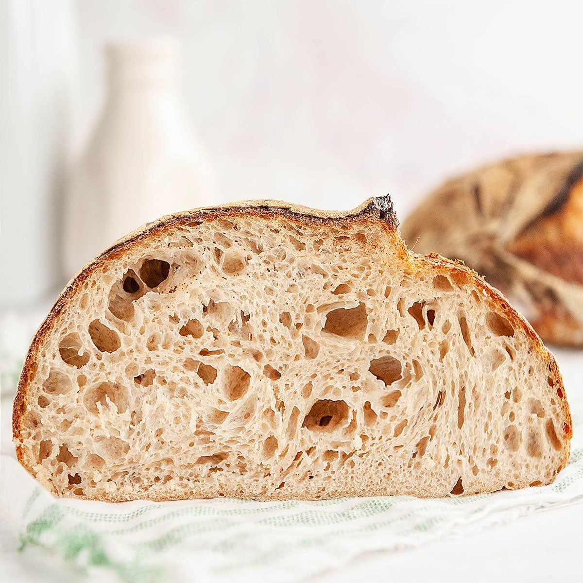 loaf of sourdough bread cut in half on white background