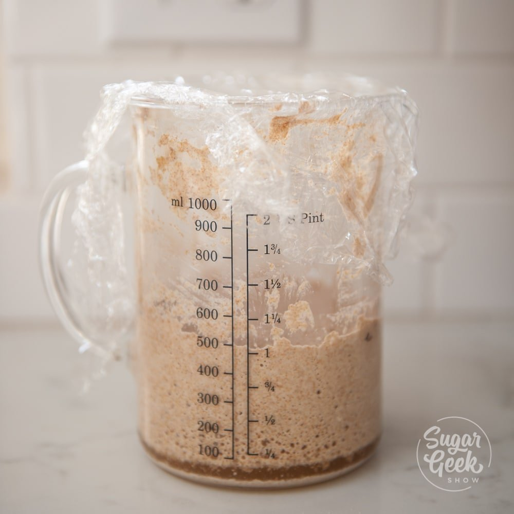 sourdough starter in clear measuring cup with plastic wrap on top