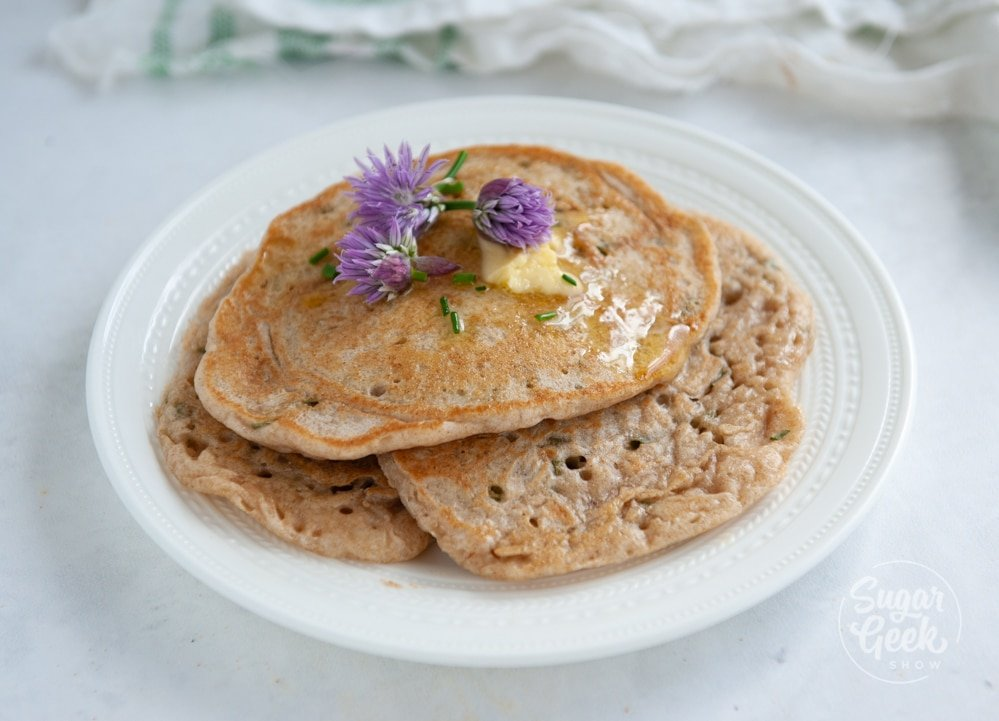 sourdough pikelets with chives on a white plate