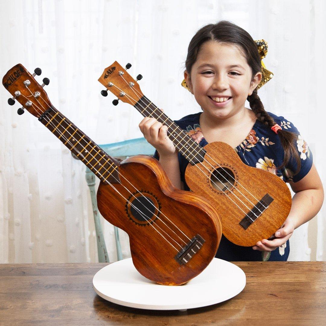 Ukulele Cake standing upright with girl holding ukulele behind to show how similar they are