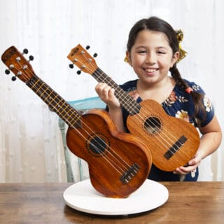 Ukulele Cake standing upright with girl holding ukulele behind to show how similar they are