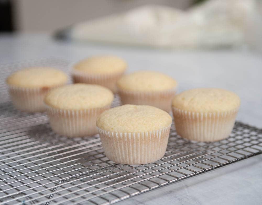 closeup of vanilla cupcakes on a cooling rack
