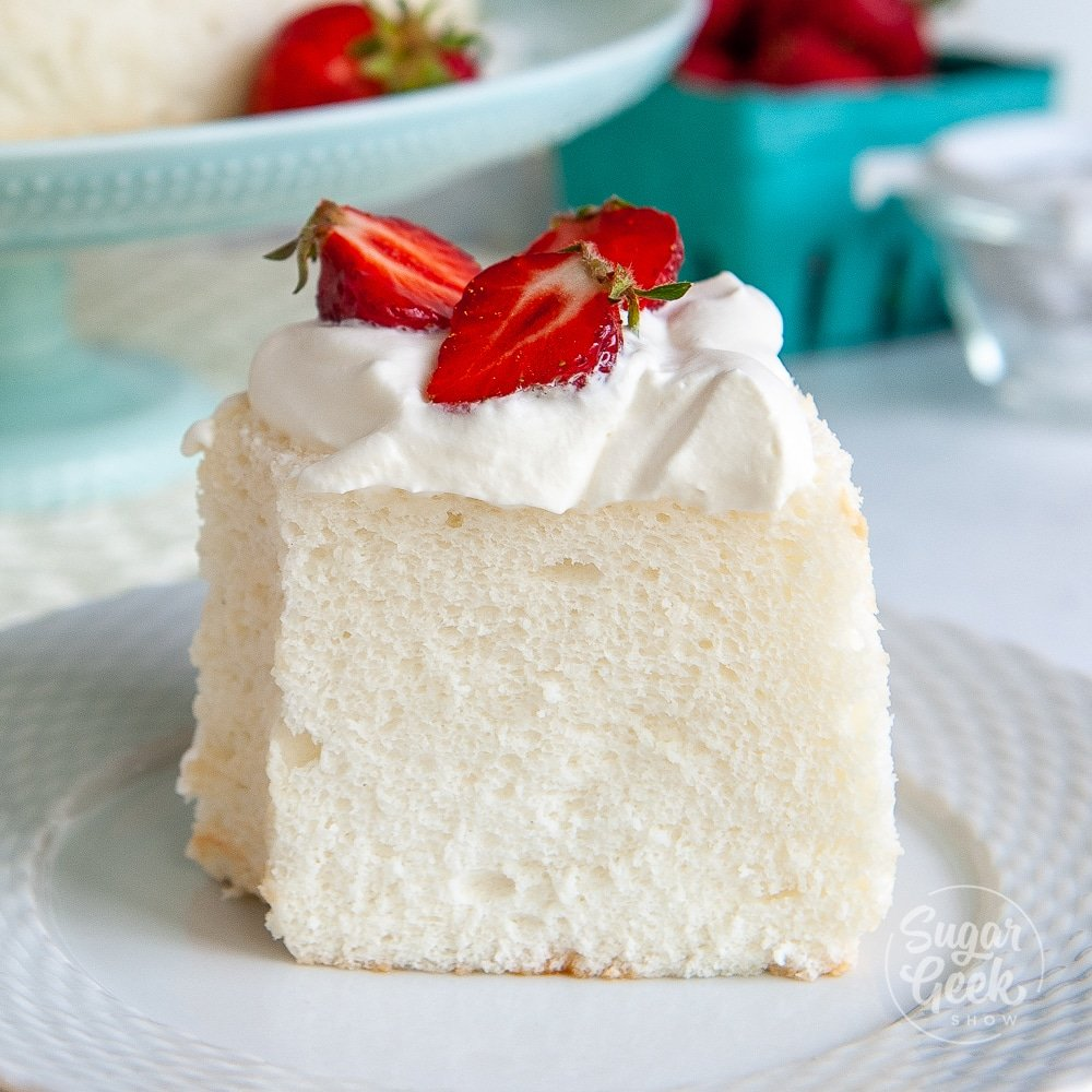 closeup of a slice of angel food cake with whipped cream and strawberries on top