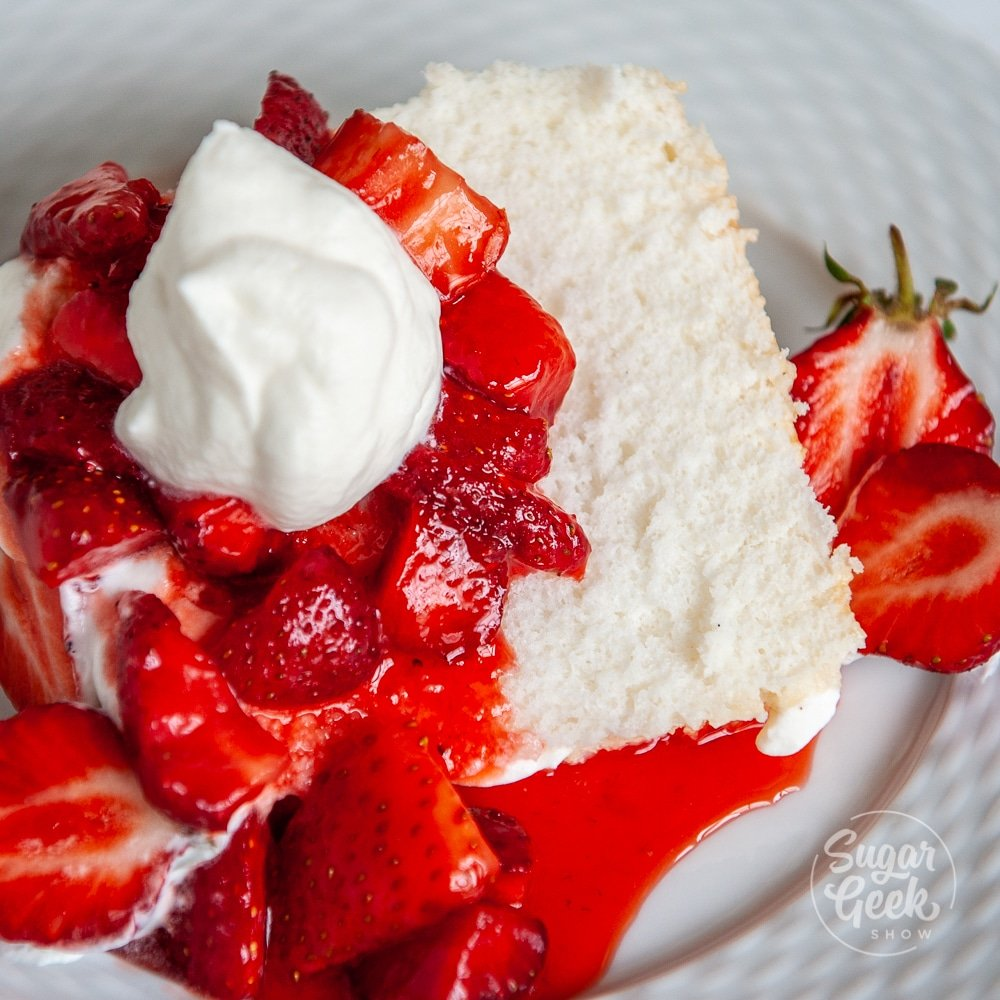 closeup of angel food cake with strawberries and whipped cream