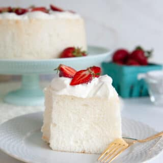 closeup of angel food cake with whipped cream and strawberries on a white plate with a gold fork. Cake in background