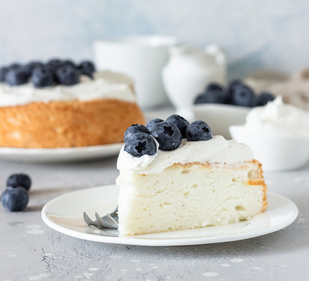 Angel food cake with whipped cream and blueberries.