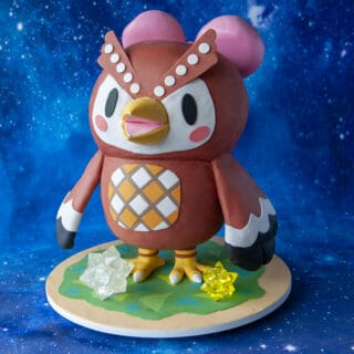 Cake sculpted into the shape of Animal Crossing character Celeste standing on a green grass cake board with isomalt star shapes