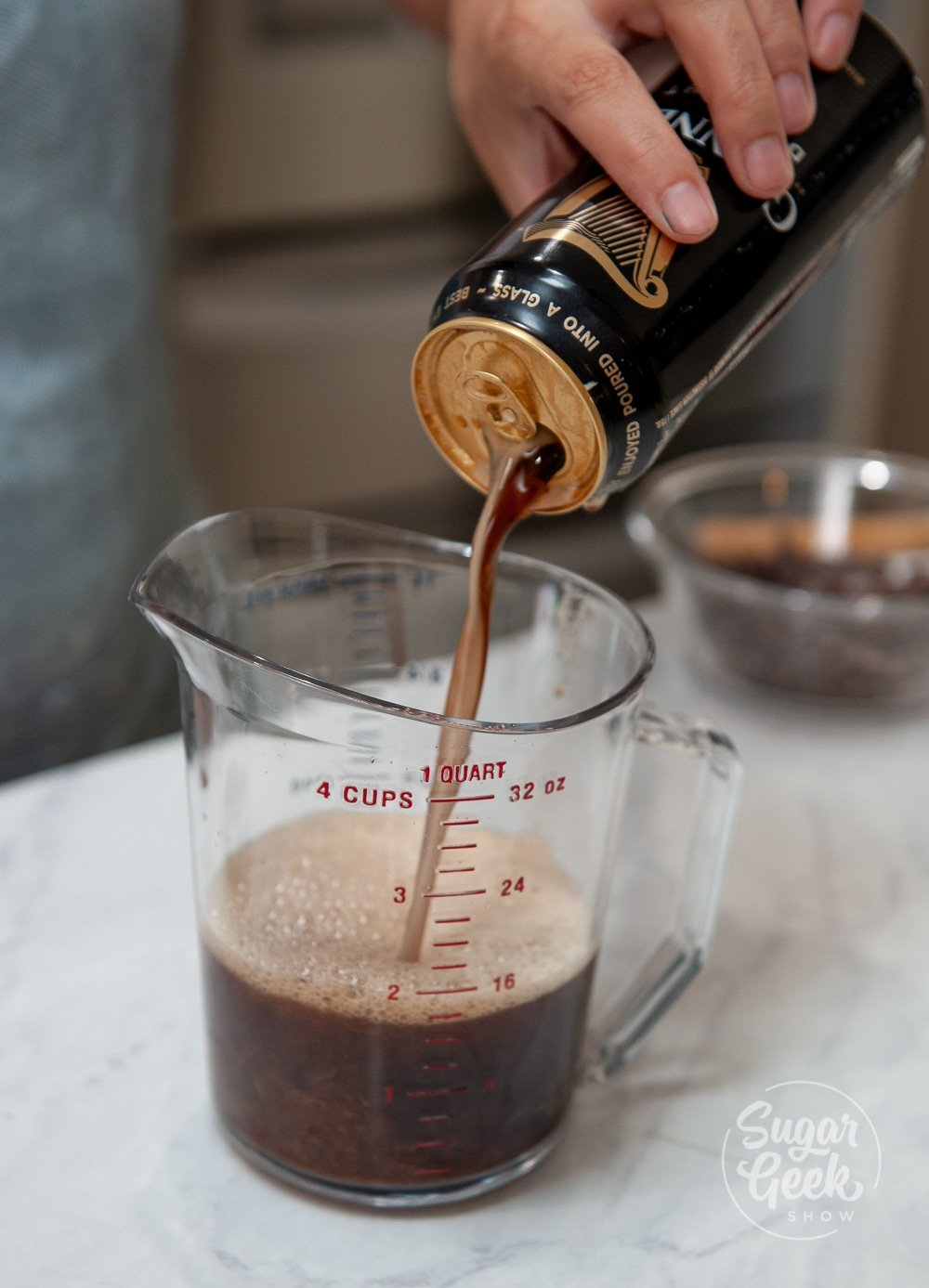 pouring dark beer into a measuring cup