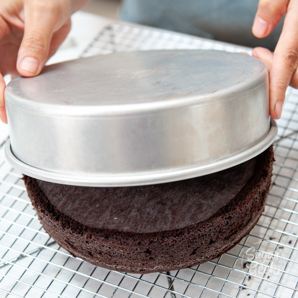 chocolate cake coming out of the pan onto a cooling rack