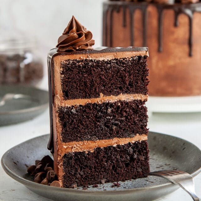 slice of chocolate cake on grey plate with cake in background