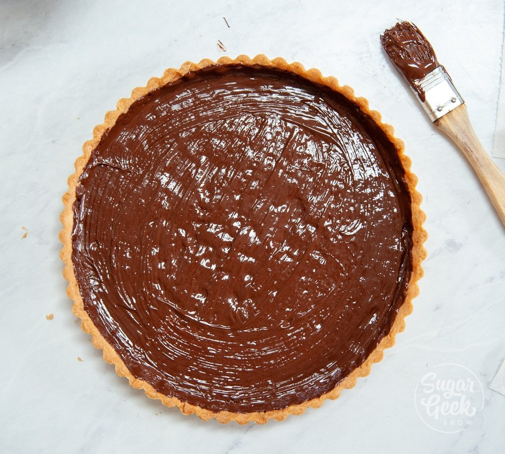melted chocolate brushed onto a tart shell