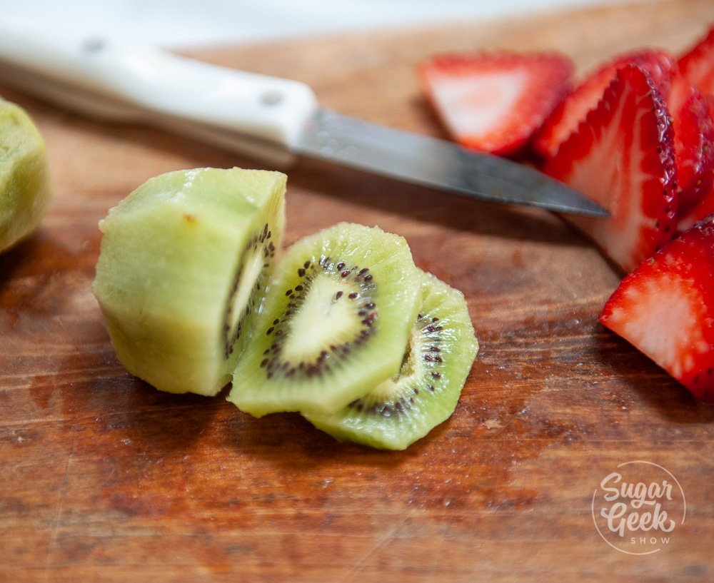 cut kiwi and strawberries on wooden cutting board