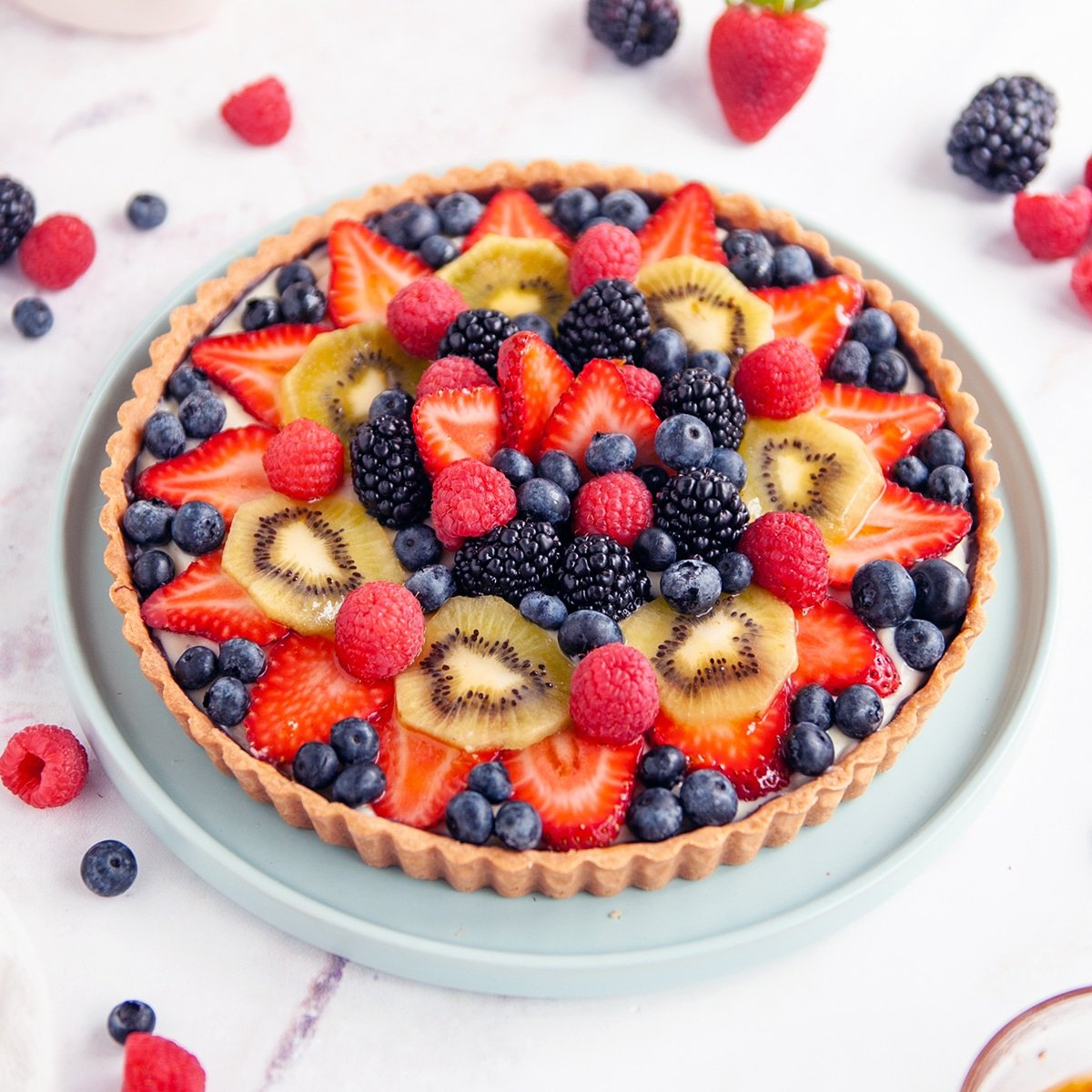 fruit tart on white background with berries surrounding