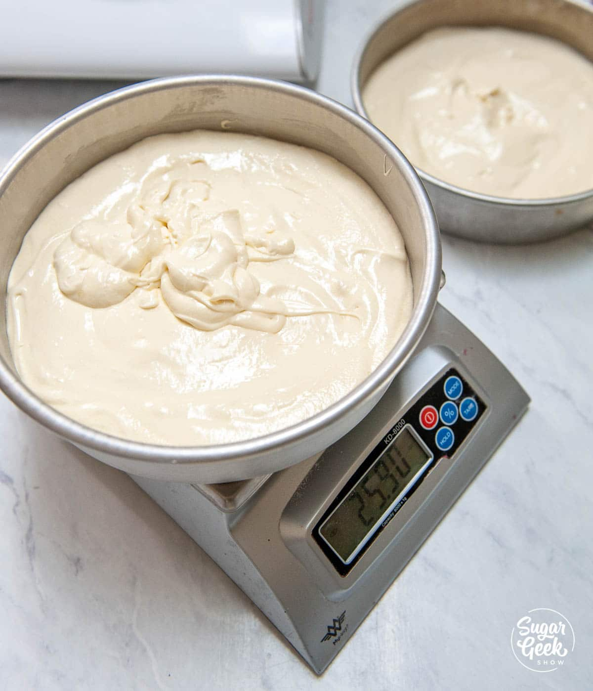 """vanilla cake in a 6"""" cake pan on a kitchen scale"""