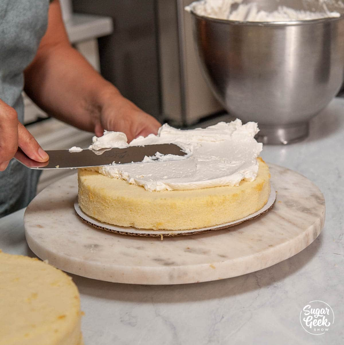 adding the first layer of easy buttercream to the vanilla cake