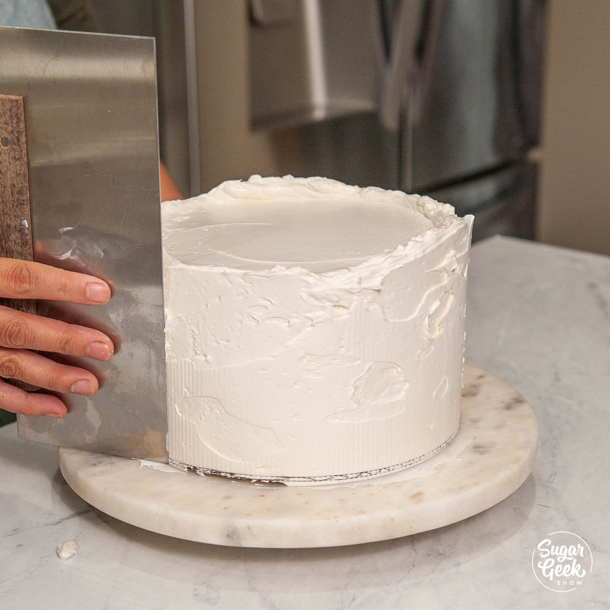 smoothing the final layer of buttercream with a bench scraper