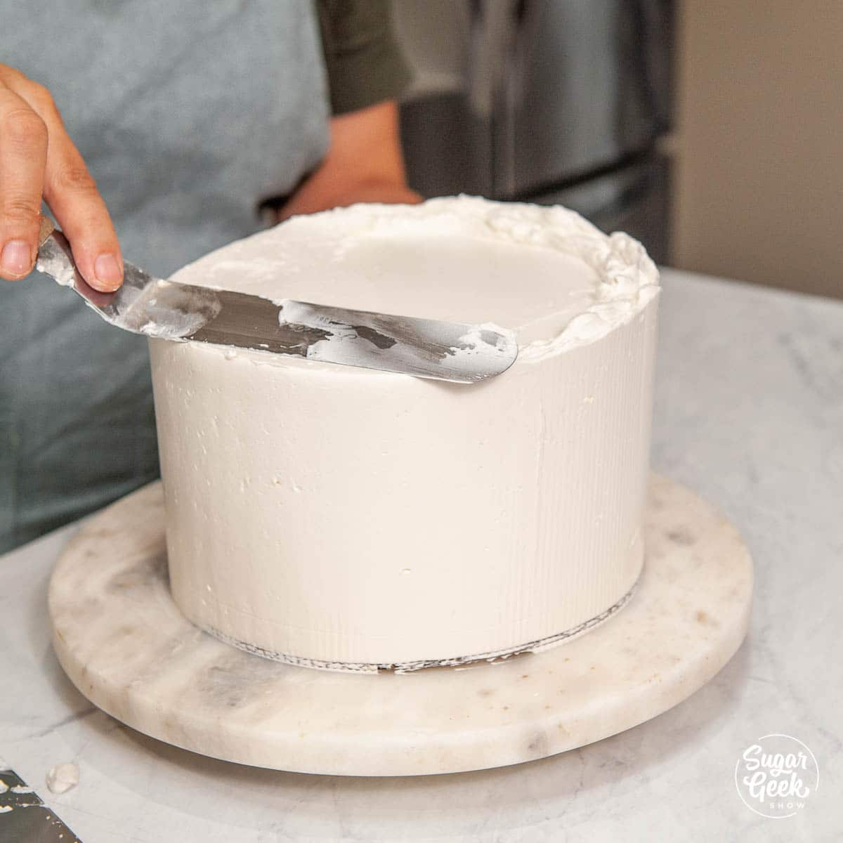 smoothing the final coat of buttercream wth an offset spatula