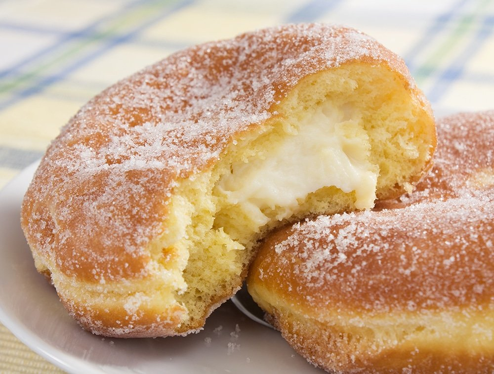 pastry cream filled donut on a white plate