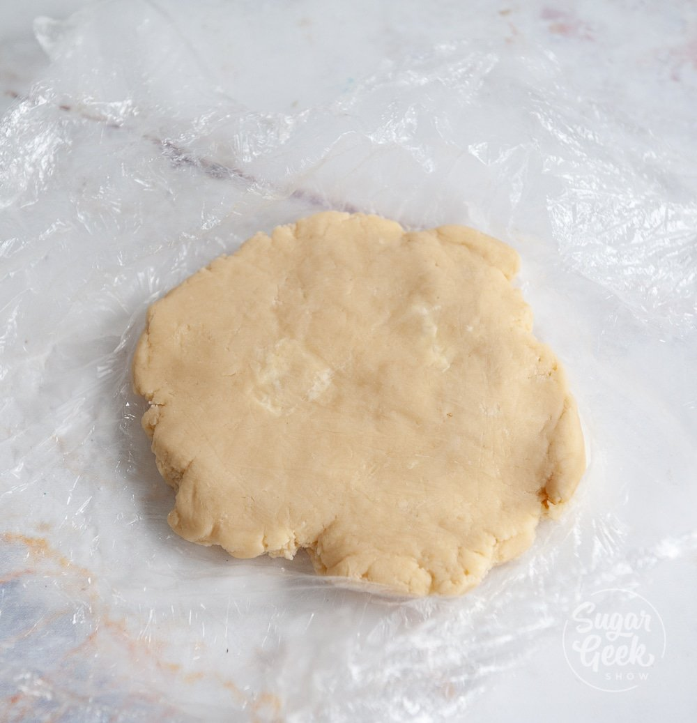 tart dough on plastic wrap on a white background