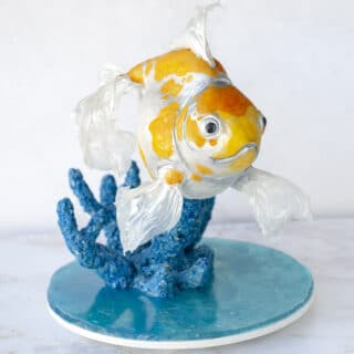 Cake sculpted into the shape of a goldfish with edible coral and a shiny isomalt cake board