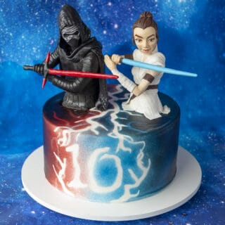 Birthday cake colored with red and blue edible airbrush color with sculpted Rey and Kylo Ren cake toppers holding lightsabers