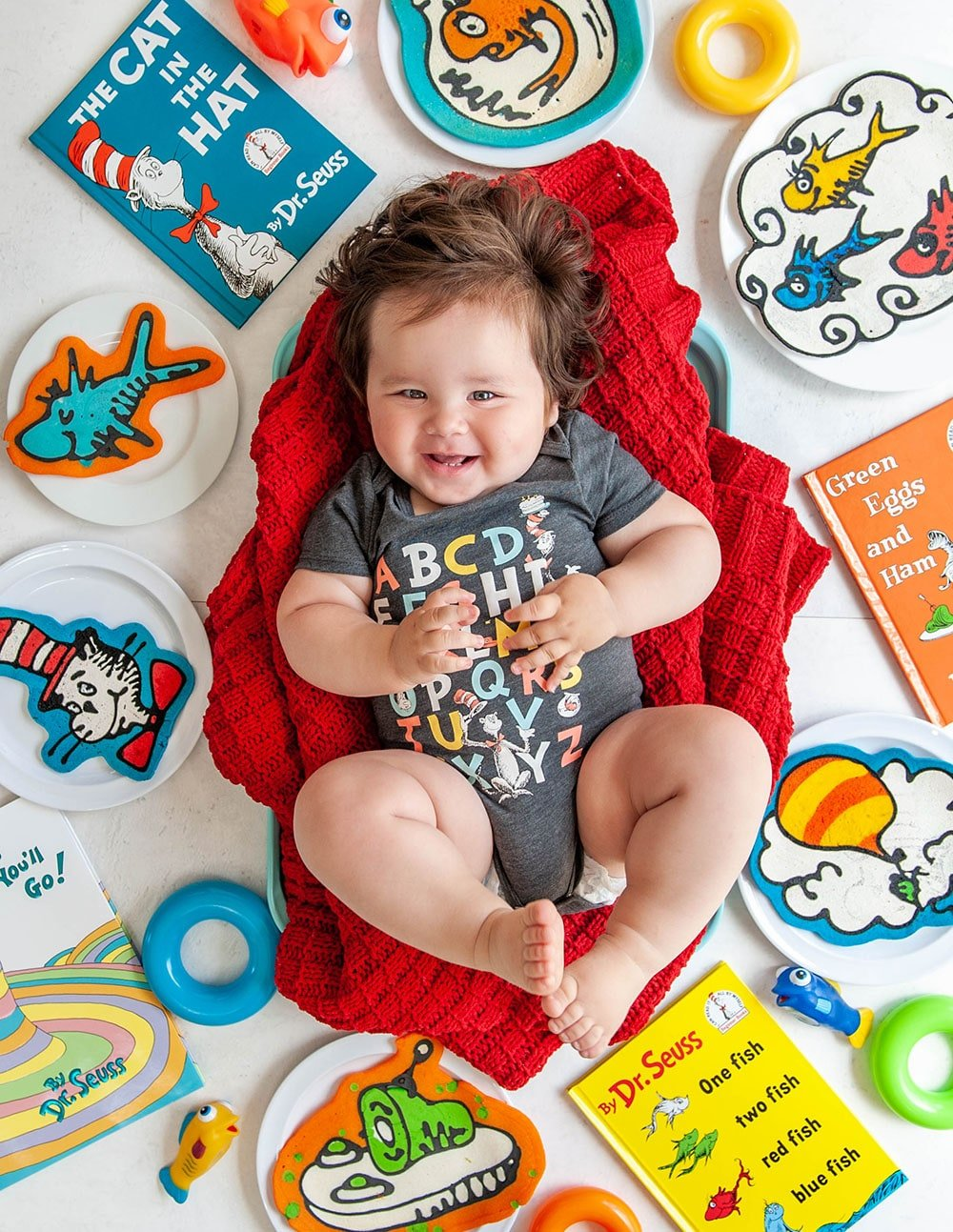 baby boy on red blanket with pancake art and dr seuss books surrounding him