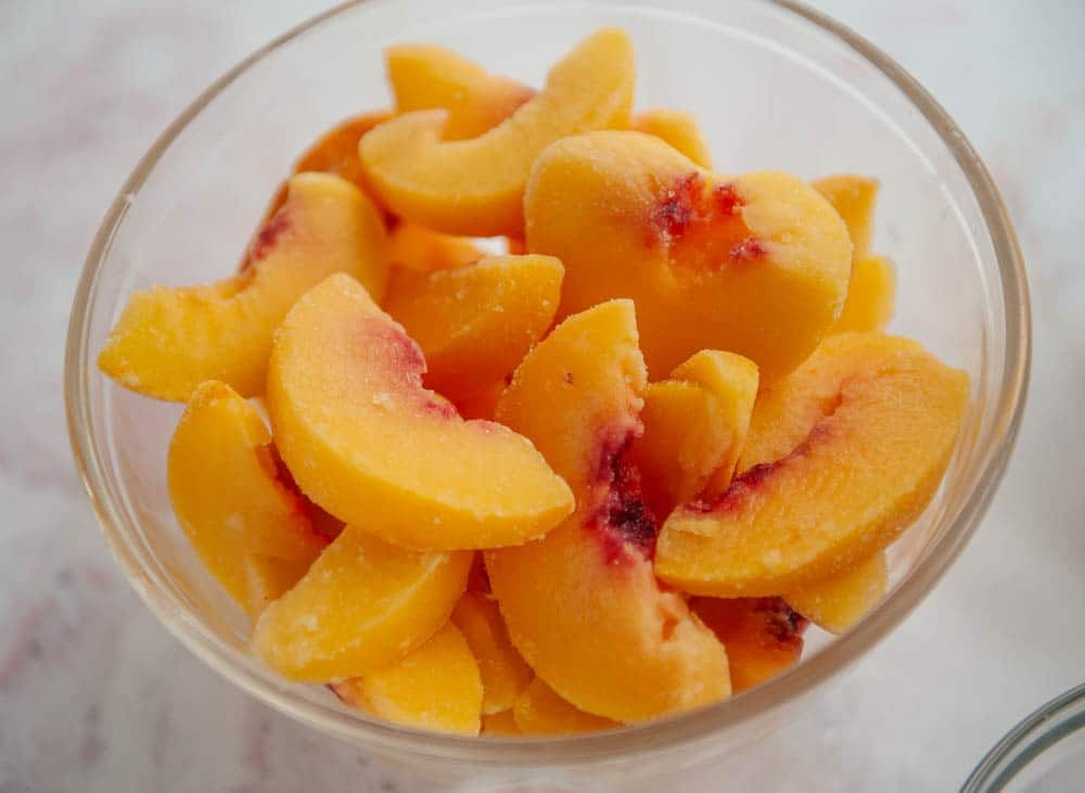 bowl of frozen peaches in clear glass bowl