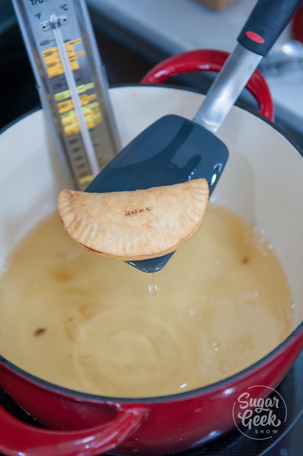 close up of a hand pie on a blue spatula above hot oil in a white pot