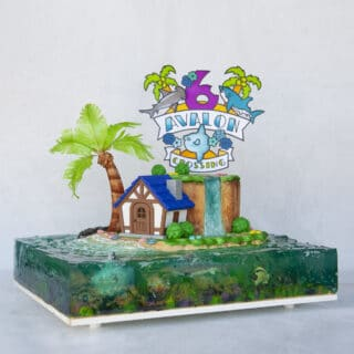 Island made out of cake with cute house, palm tree, cake topper and jelly ocean surrounding island