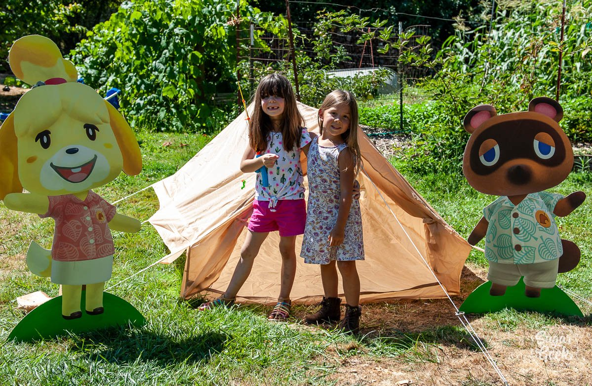 two girls standing in front of a tan a-frame tent with isabelle and tom nook on the sides