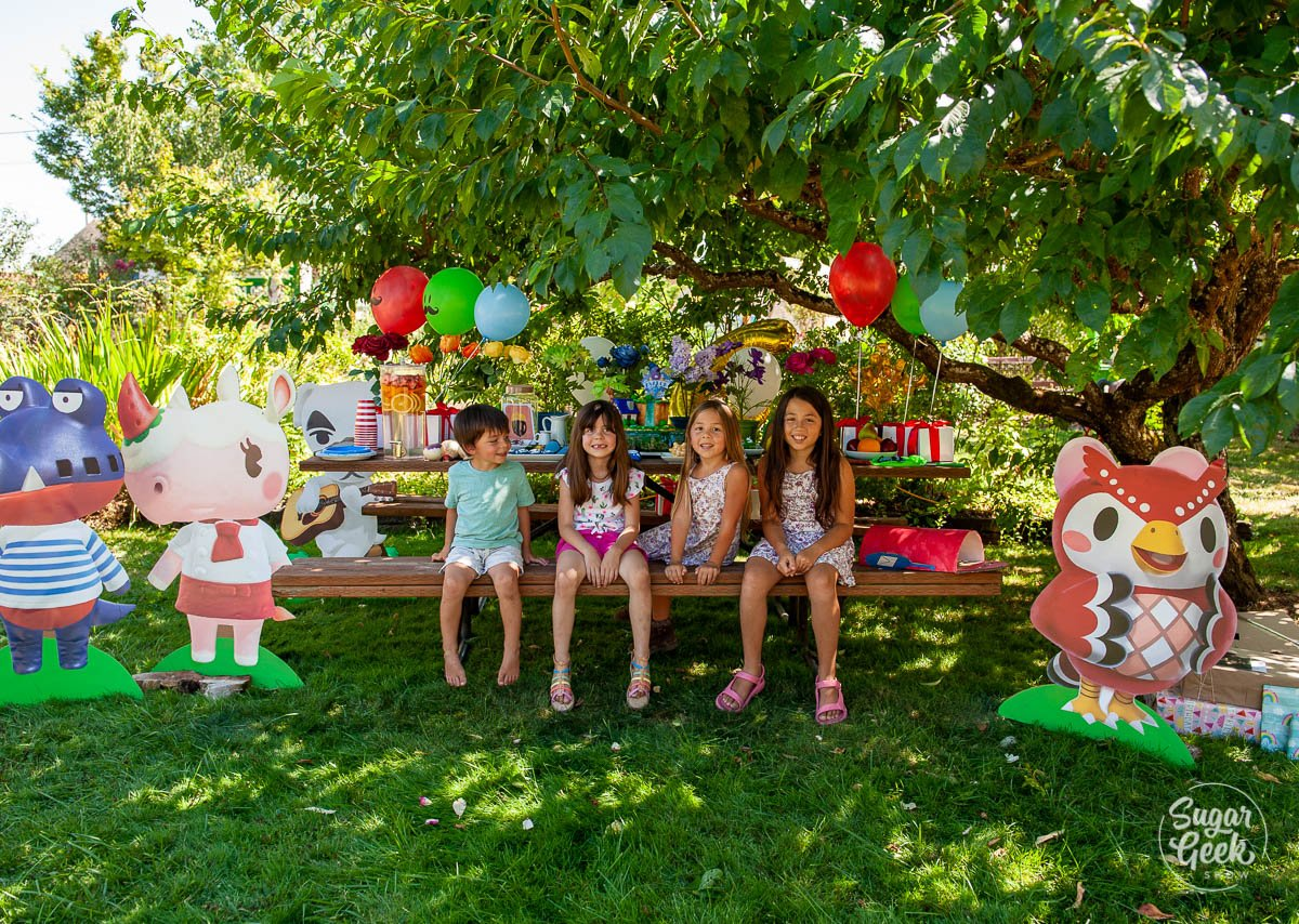 four kids sitting on a picnic bench with birthday decorations under a tree