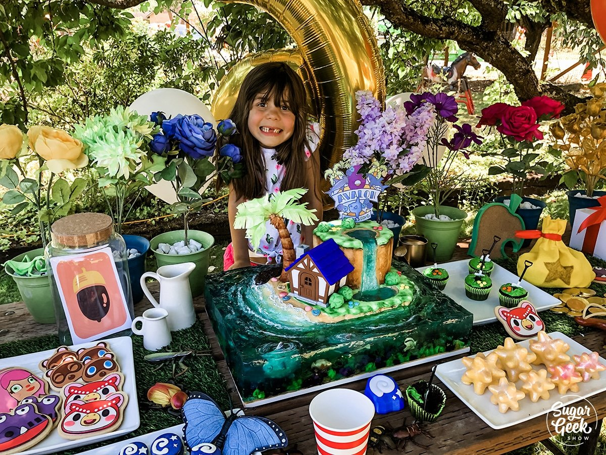 child sitting behind a table filled with animal crossing desserts