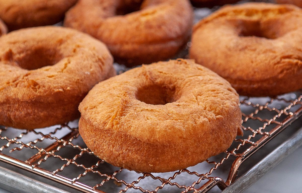 close up of fried cake donuts on a cooling rack