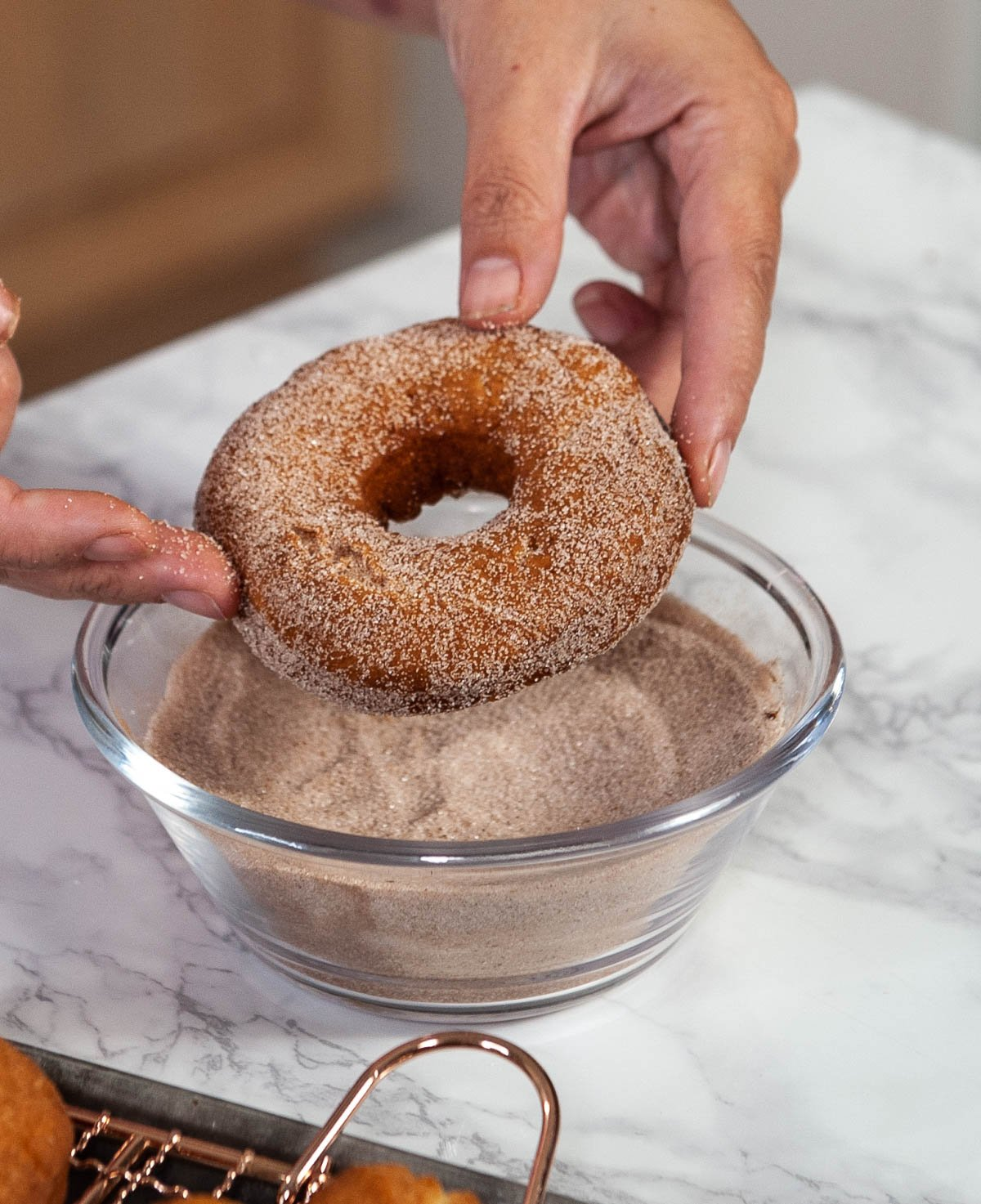 donut being held above a glass bowl of cinnamon sugar