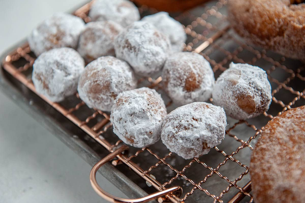 donut holes covered in powdered sugar on a cooling rack