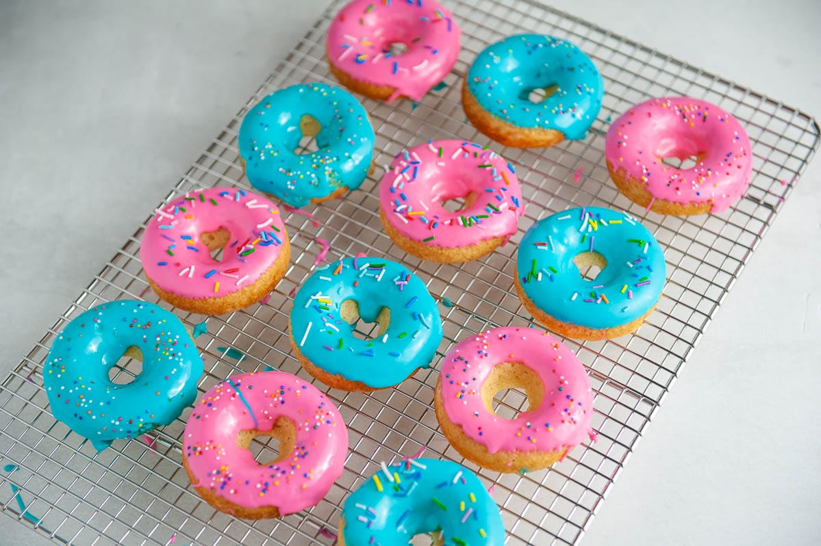 pink and blue glazed donuts with sprinkles on a cooling rack