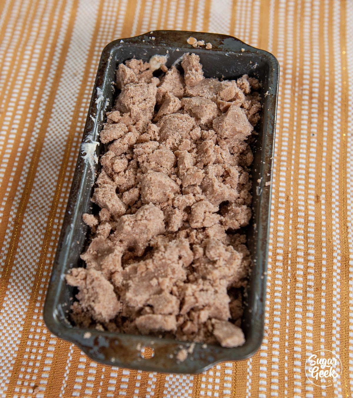 adding cake crumbs on top of coffee cake batter in loaf pan