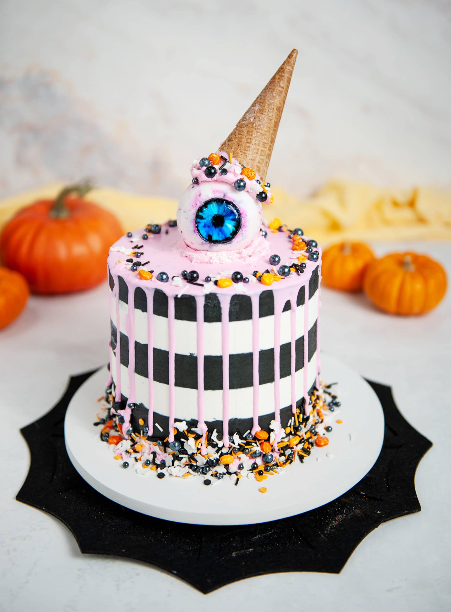 black and white striped cake with pink drip, gummy eyeball with ice cream cone on top