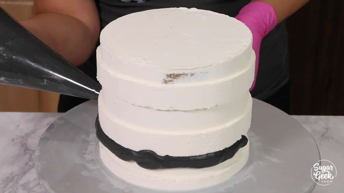 adding black buttercream stripes to white buttercream cake with a piping bag